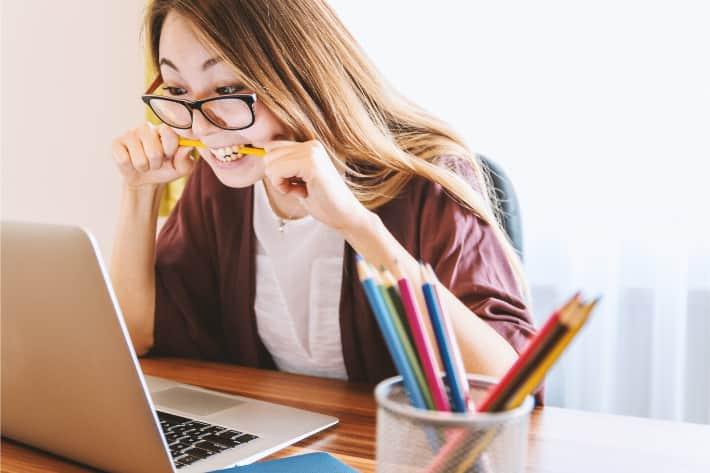 Kvinna som biter i en penna i frustration över bärbar dator