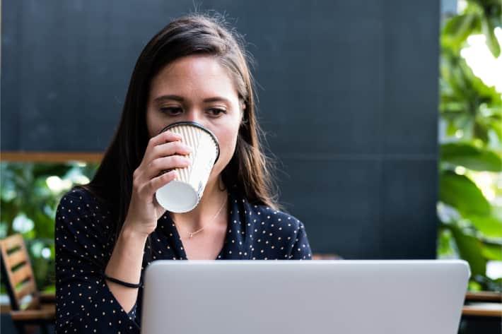 Kvinna som surfar på bärbar dator och dricker kaffe